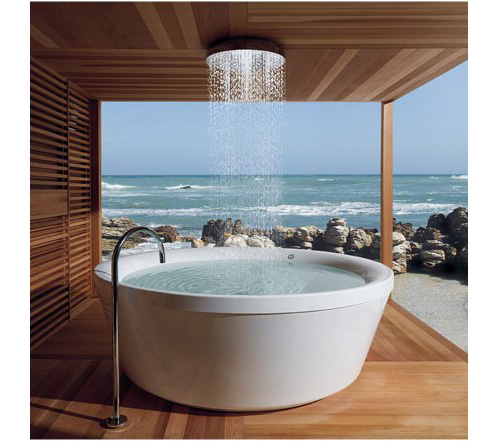 Round bathtub and shower on a wooden decking overlooking the sea
