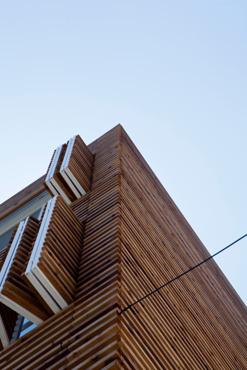 Wood Used For Elevation : House covered in horizontal slats with louvered windows by