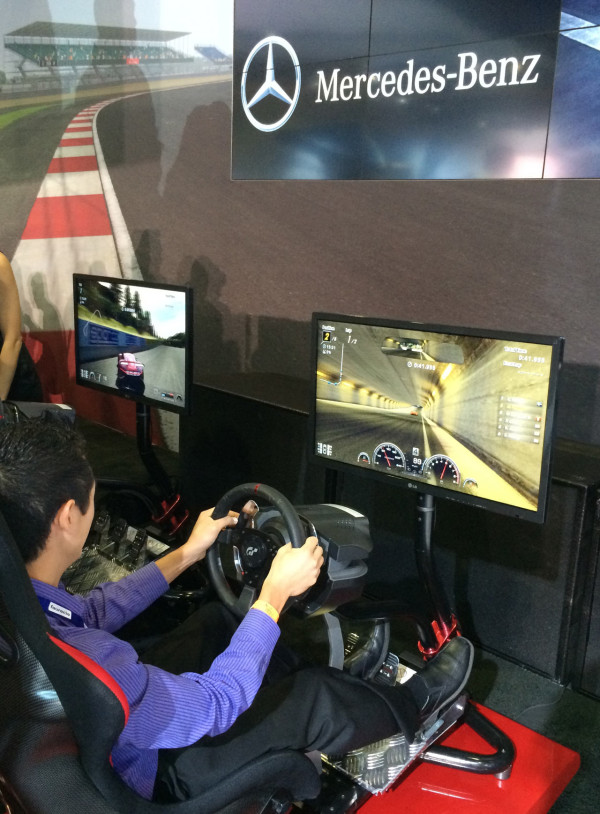 An LA Auto Show attendee drives the Mercedes in Gran Turismo 6
