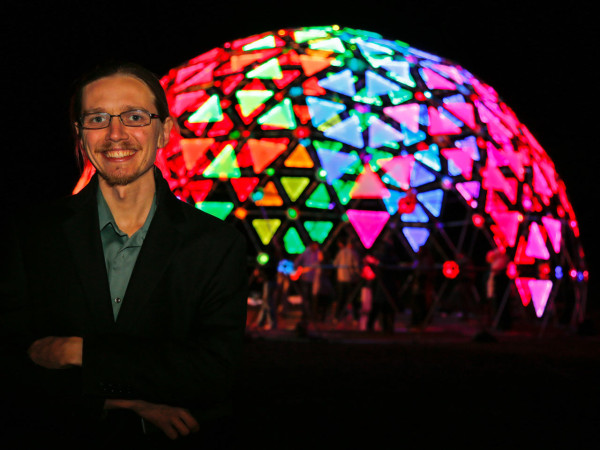 Yona Appletree poses in front of the illuminated Radiance Dome