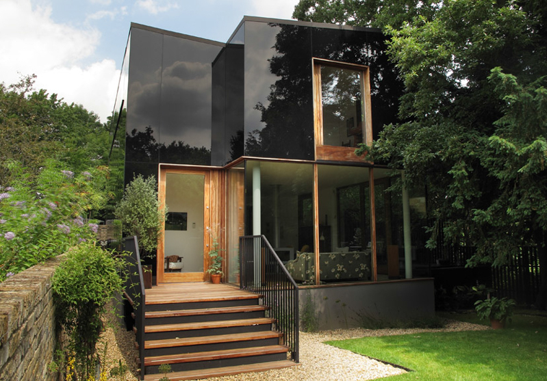 Striking Black Glass Home Mirrors Its Rich Surroundings