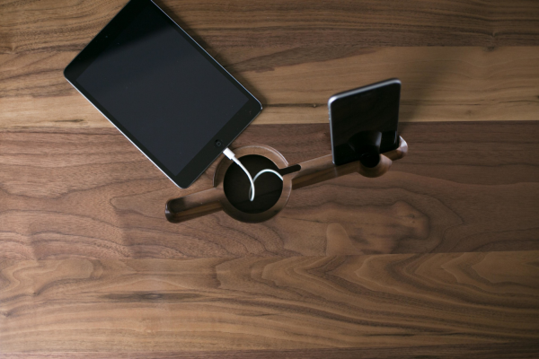 An integrated angled mobile device slot is designed to both keep screens upright in view and hide away connecting cables through a porthole.