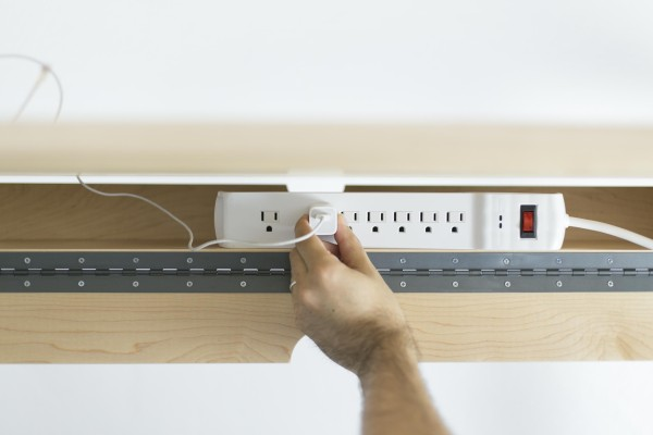A storage cabinet designed to hide away a power strip is easily accessible for plugging in, but otherwise keeps the usual eyesore out of view.