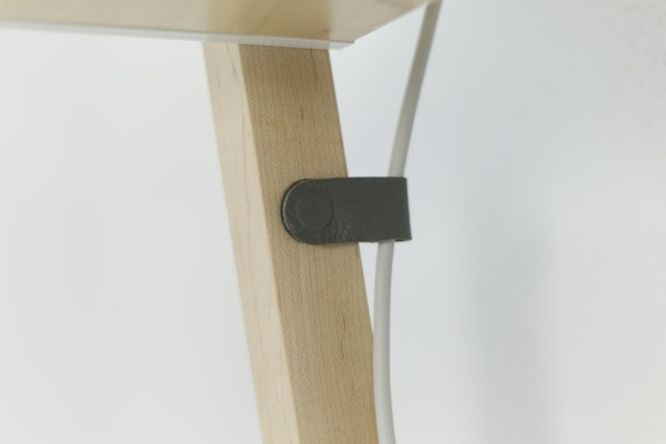 A magnetic leather snap routes cords and cables down the desk's legs.