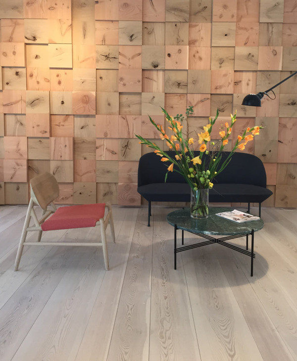 A corner of the Dinesen showroom that uses wood on the floors and wood pieces to cover the wall like a mosaic.