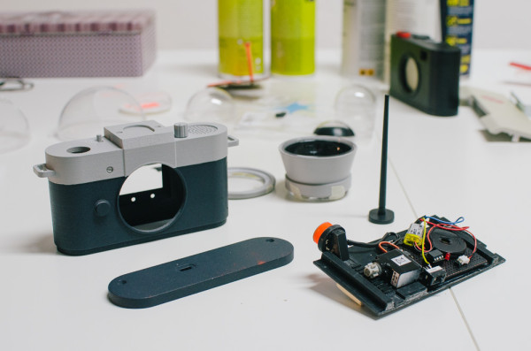 The Camera Restricta's 3D-printed camera body houses  a ATTiny85 microcontroller, alongside a  smartphone for handling GPS, geotagging queries, and for the camera screen.