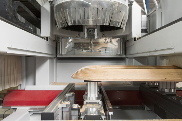 A five-axis CNC machine is used to mill the underside of the table top.