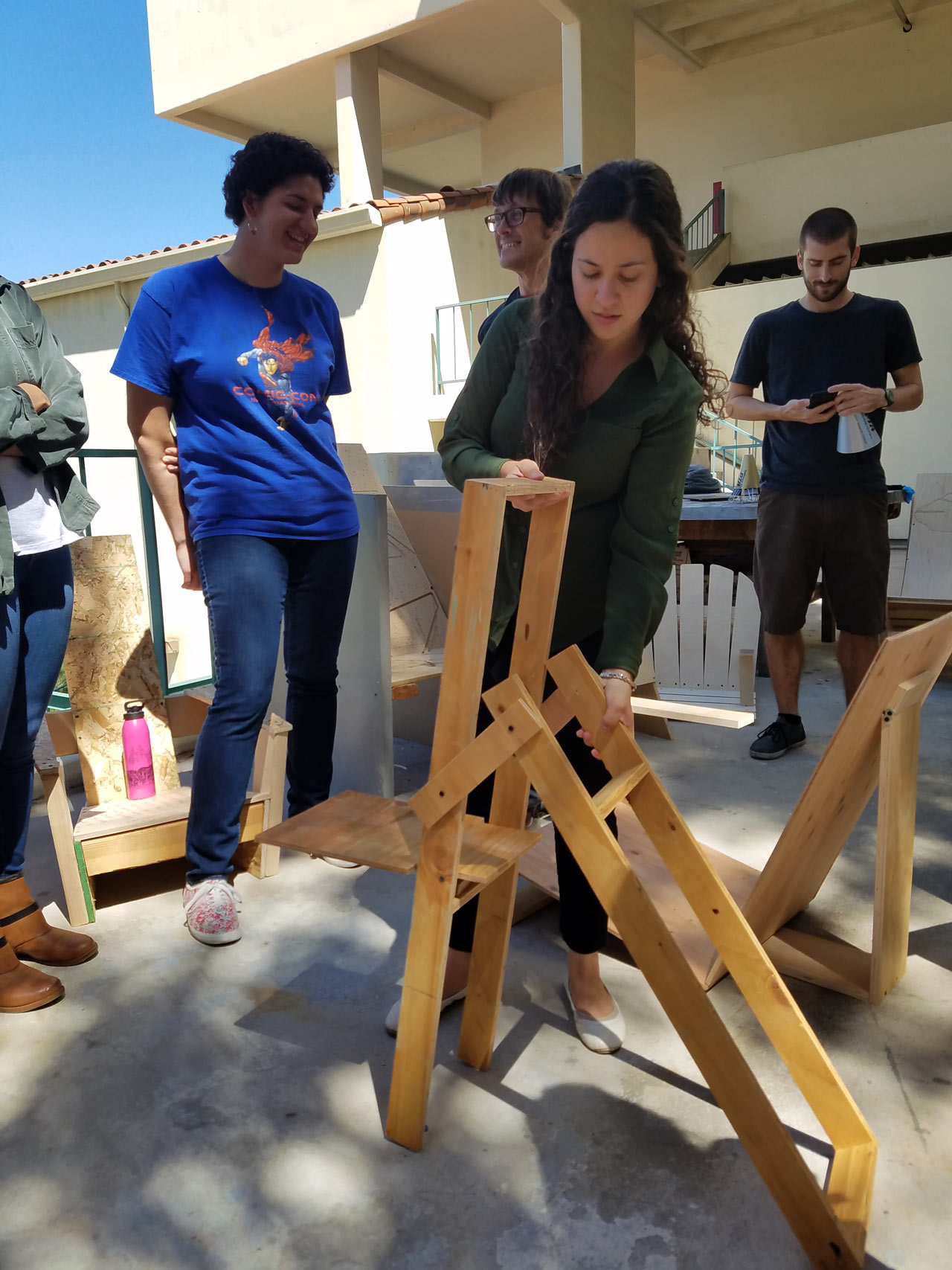 Caselle Reinke demonstrates her folding chair during the critique. Photo by Aleya Lanteigne