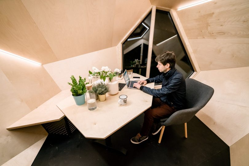 Person working at table in Workstation Cabin