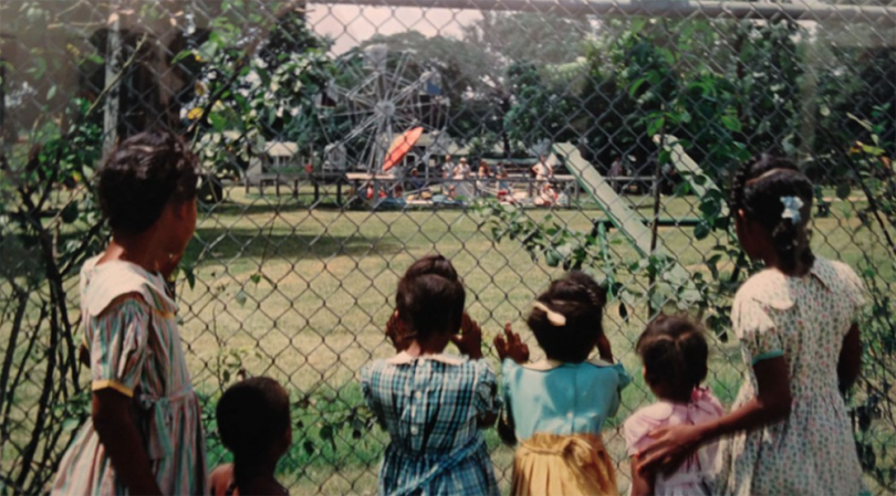 children looking through chainlink fence