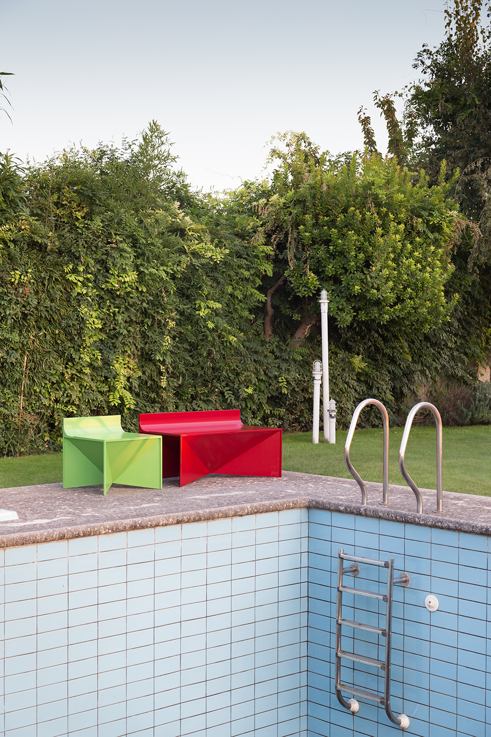 metal outdoor chair and bench by pool