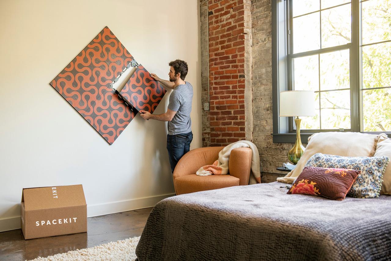 man installing art in bedroom