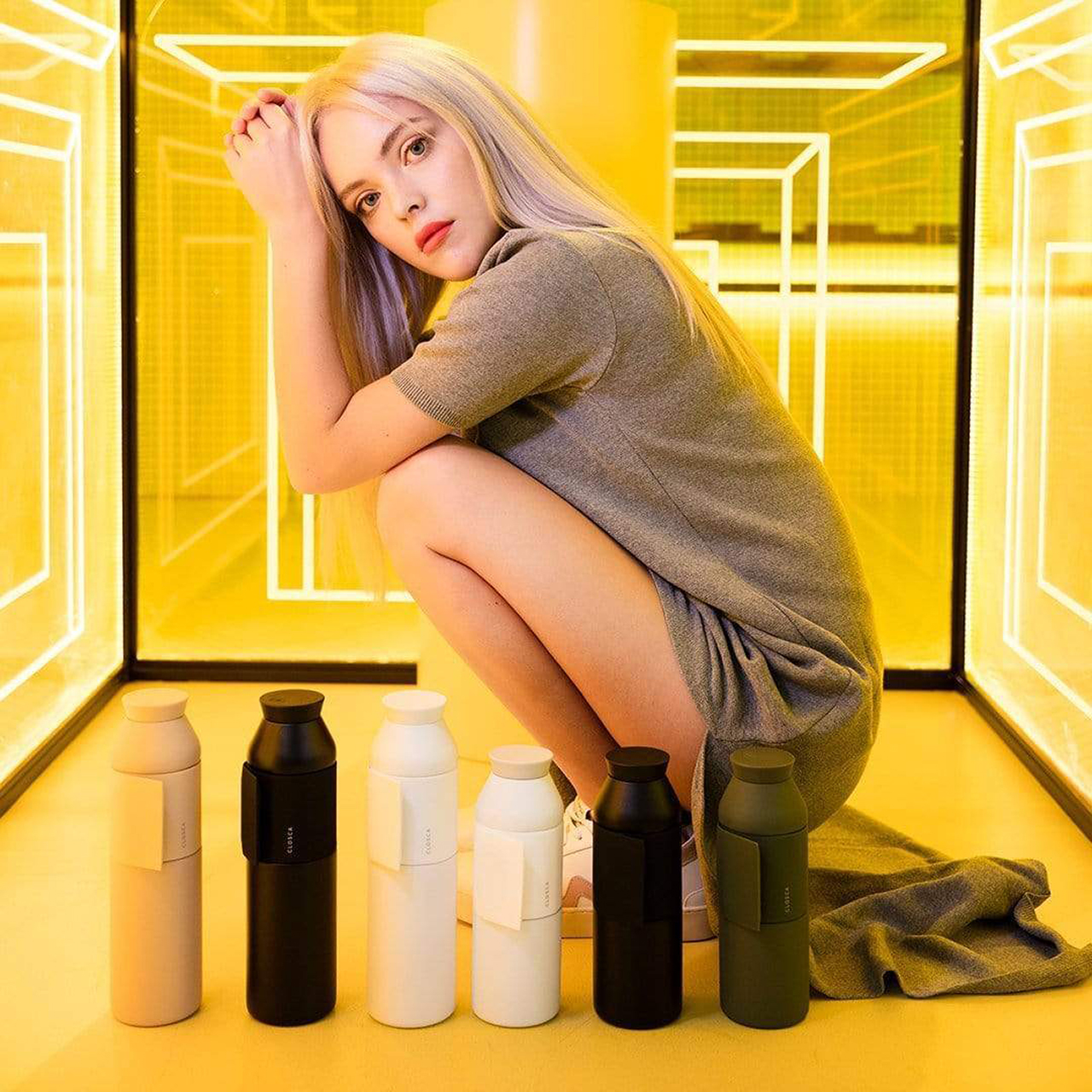 woman crouched next to six water bottles