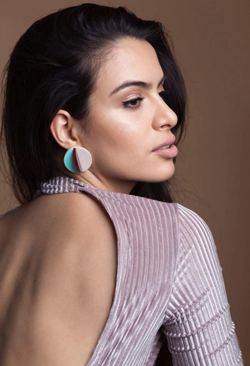 woman wearing open back sweater and earring