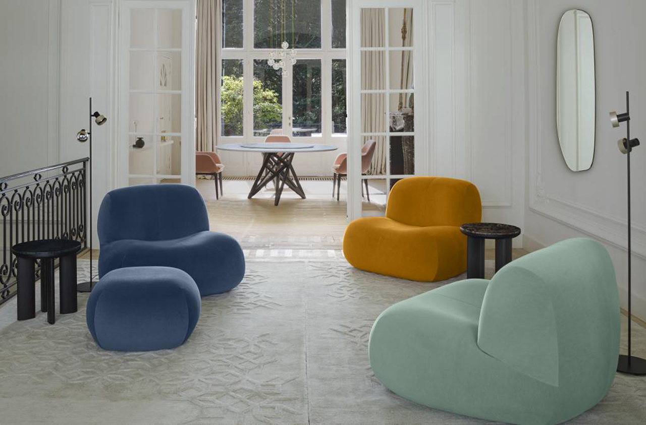 living space with three chairs and pouf