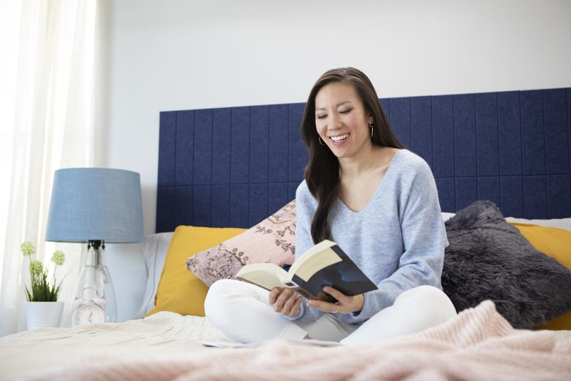 woman sitting in bed reading