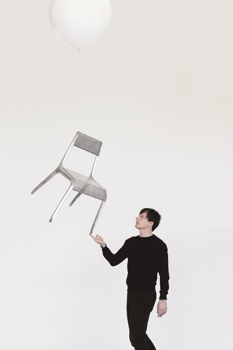 man holding up chair with finger