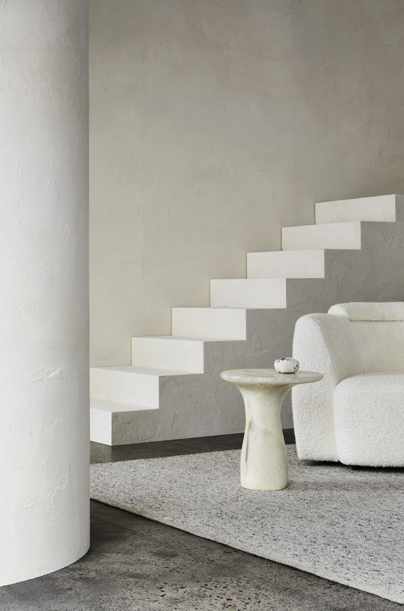 armchair and end table in front of staircase