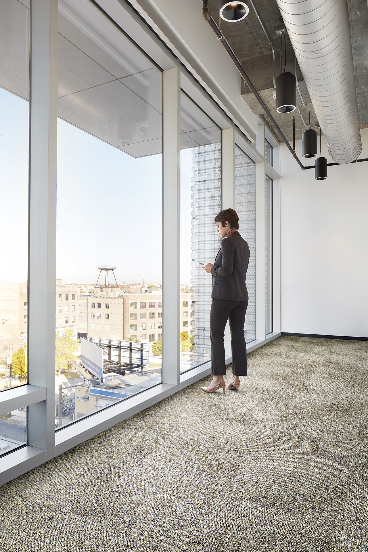 woman standing in front of large windows