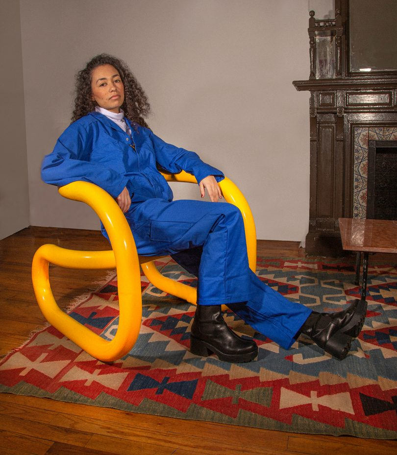 woman sitting in sculptural chair in living space