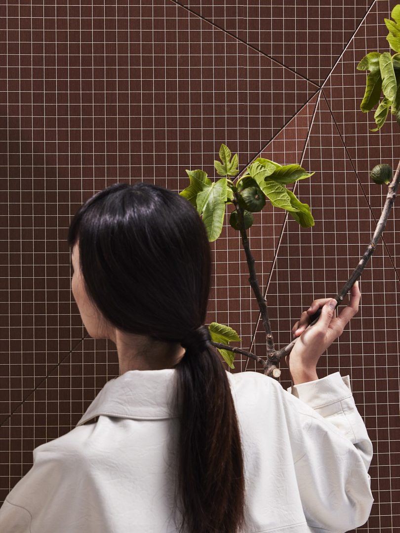close up of back of woman holding branch standing in front of faceted wall panel