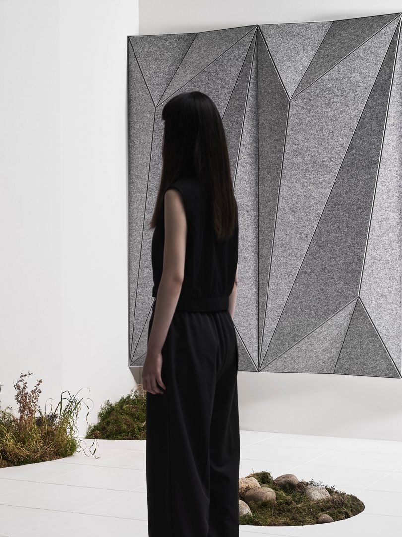 woman facing away from camera in a room with white walls and floor and faceted wall panels