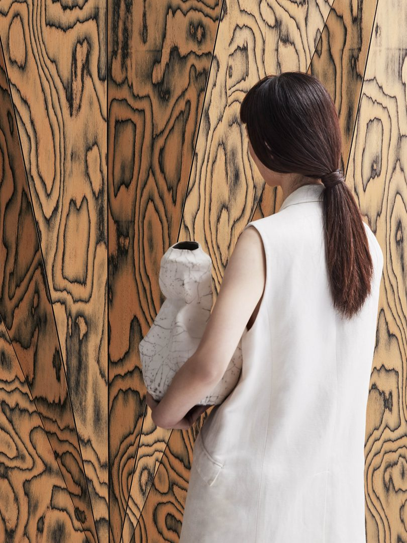 close up of back of woman holding vase standing in front of faceted wall panel