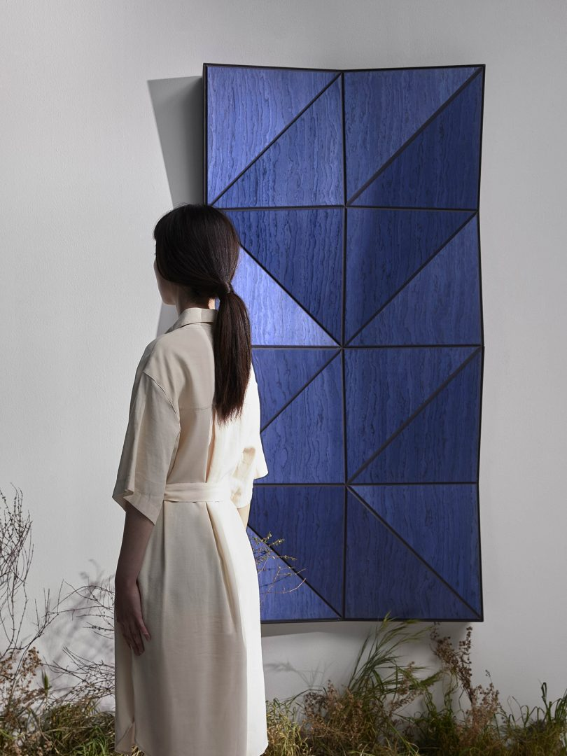 woman standing backwards in front of blue faceted wall panels