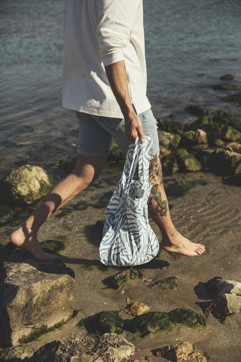 man walking on shore with tote
