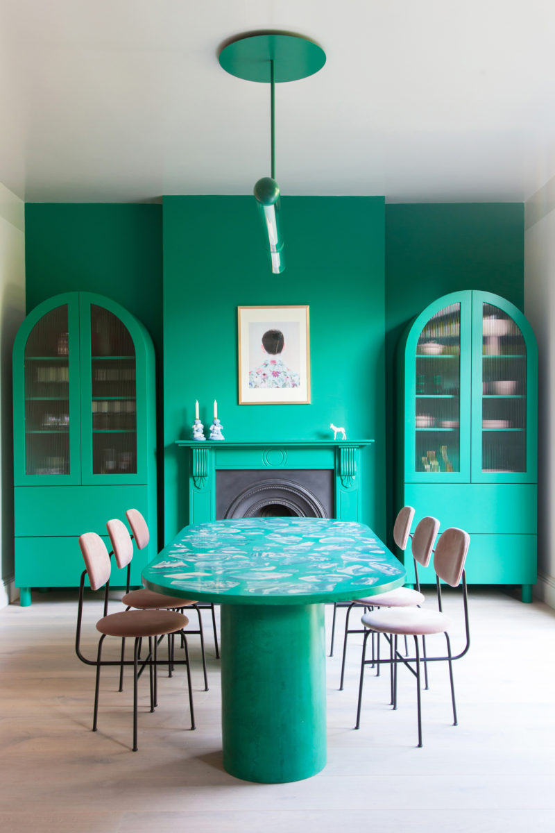 green dining room with pink chairs