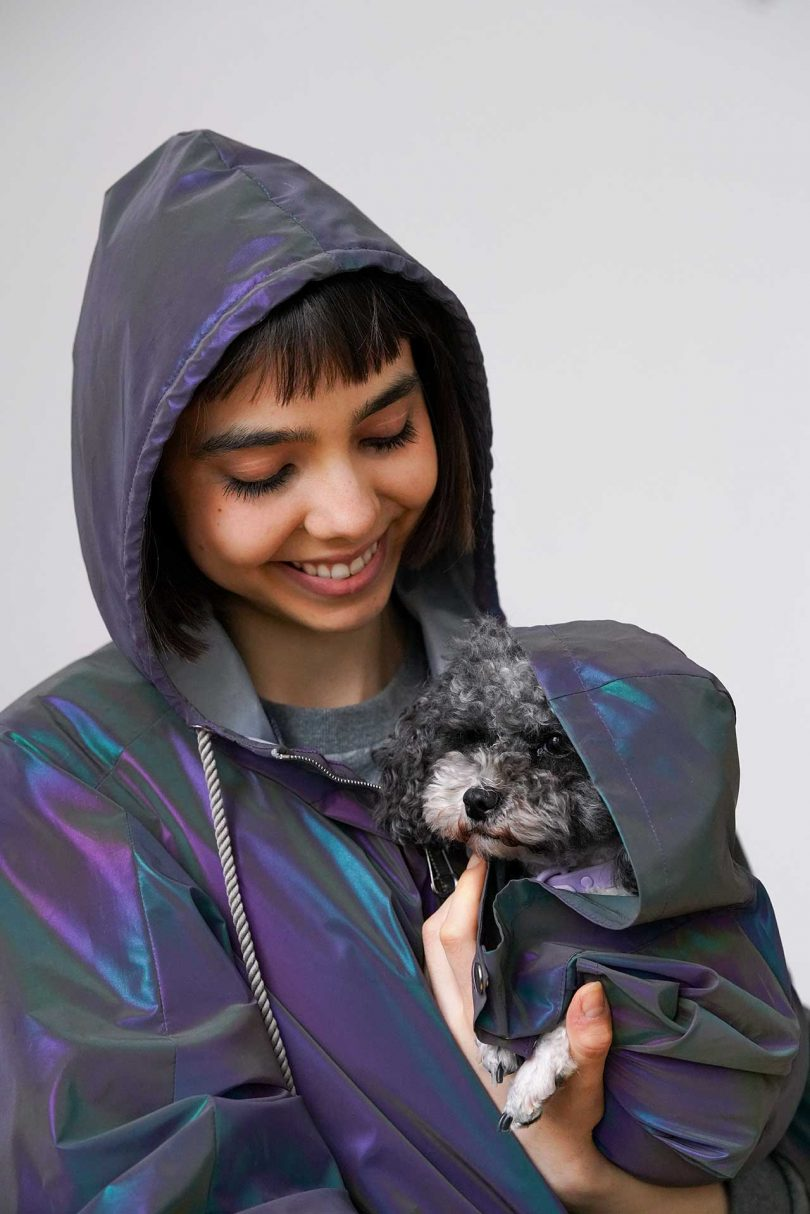 person holding a dog in matching raincoats