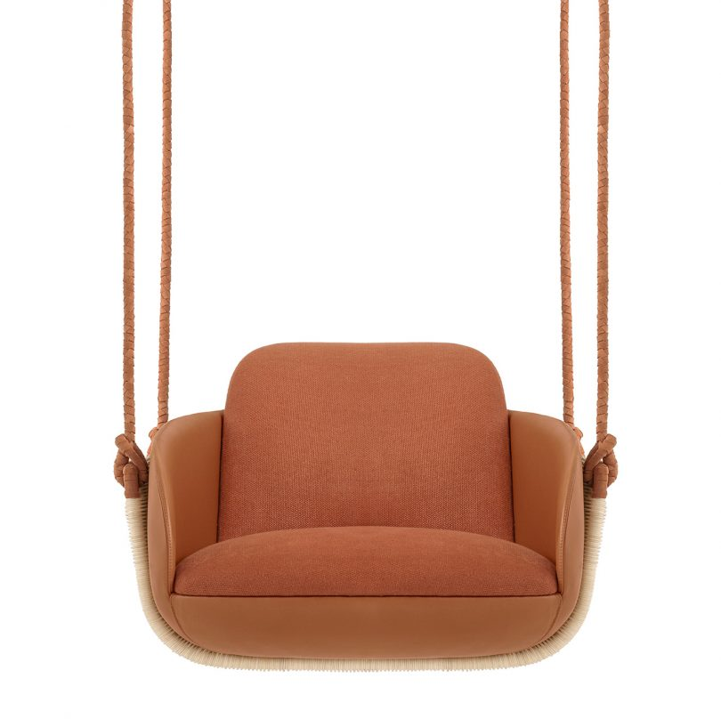 front view of hanging chair with rust upholstery on white background