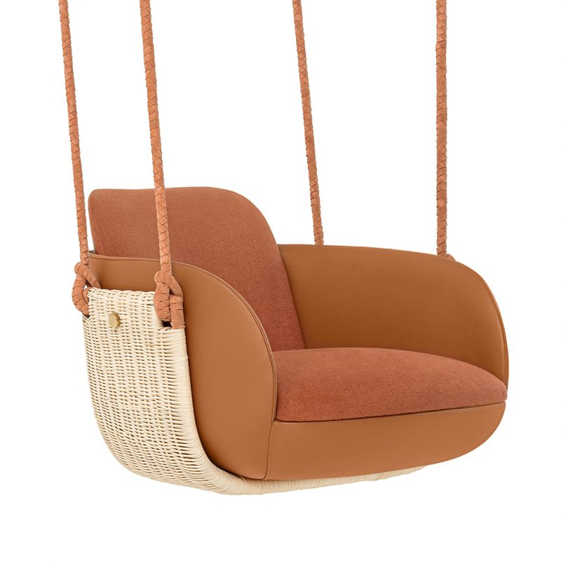 three quarter view of hanging chair with rust upholstery on white background