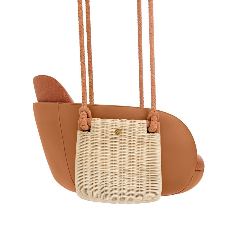 side view of hanging chair with rust upholstery on white background