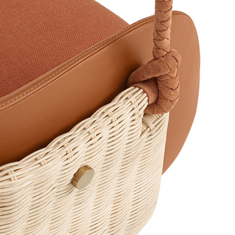 detail photo of hanging chair with rust upholstery on white background