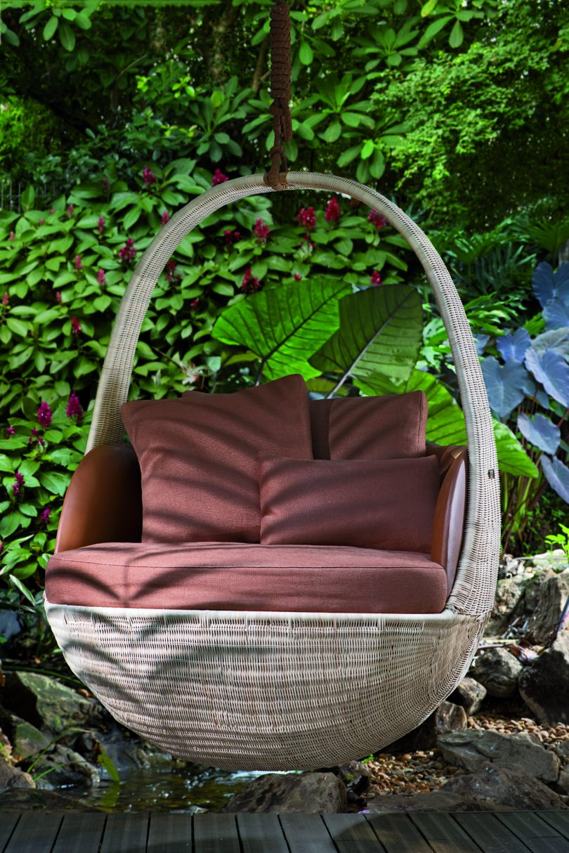 hanging chair with rust upholstery suspended outdoors
