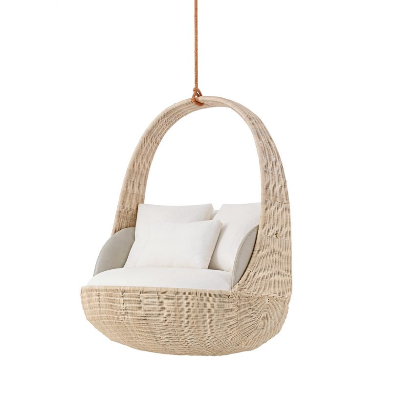 three quarter view of hanging chair with white upholstery on white background