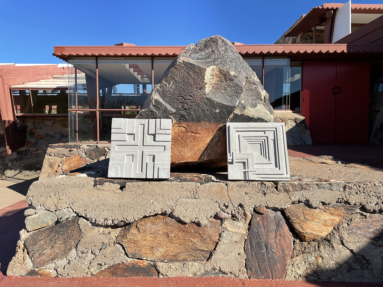two cement tiles leaning against a rock with a building and blue skies in the background