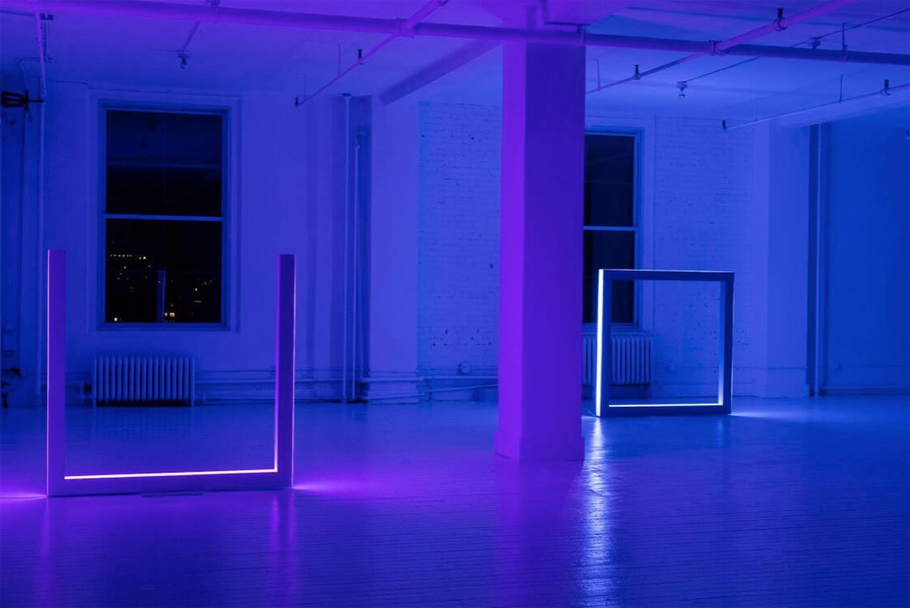 illuminated art gallery with two box-like sculptures