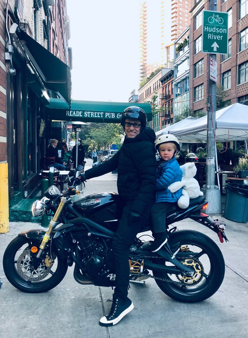 man and young child sitting on motorcycle on city street