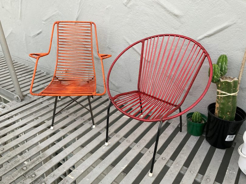 one orange chair and one red chair on slatted balcony