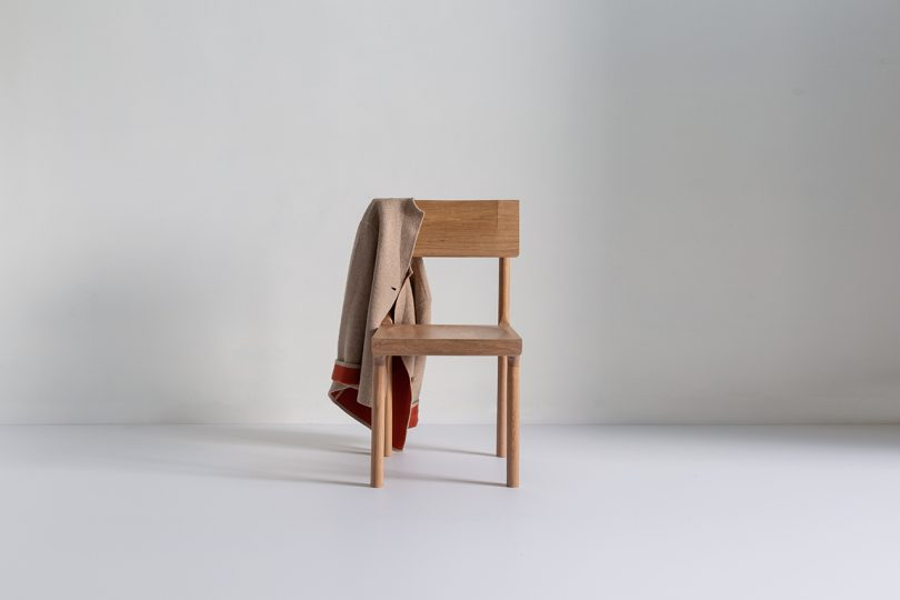 Oak dining chair with garment hanging on it on a white background