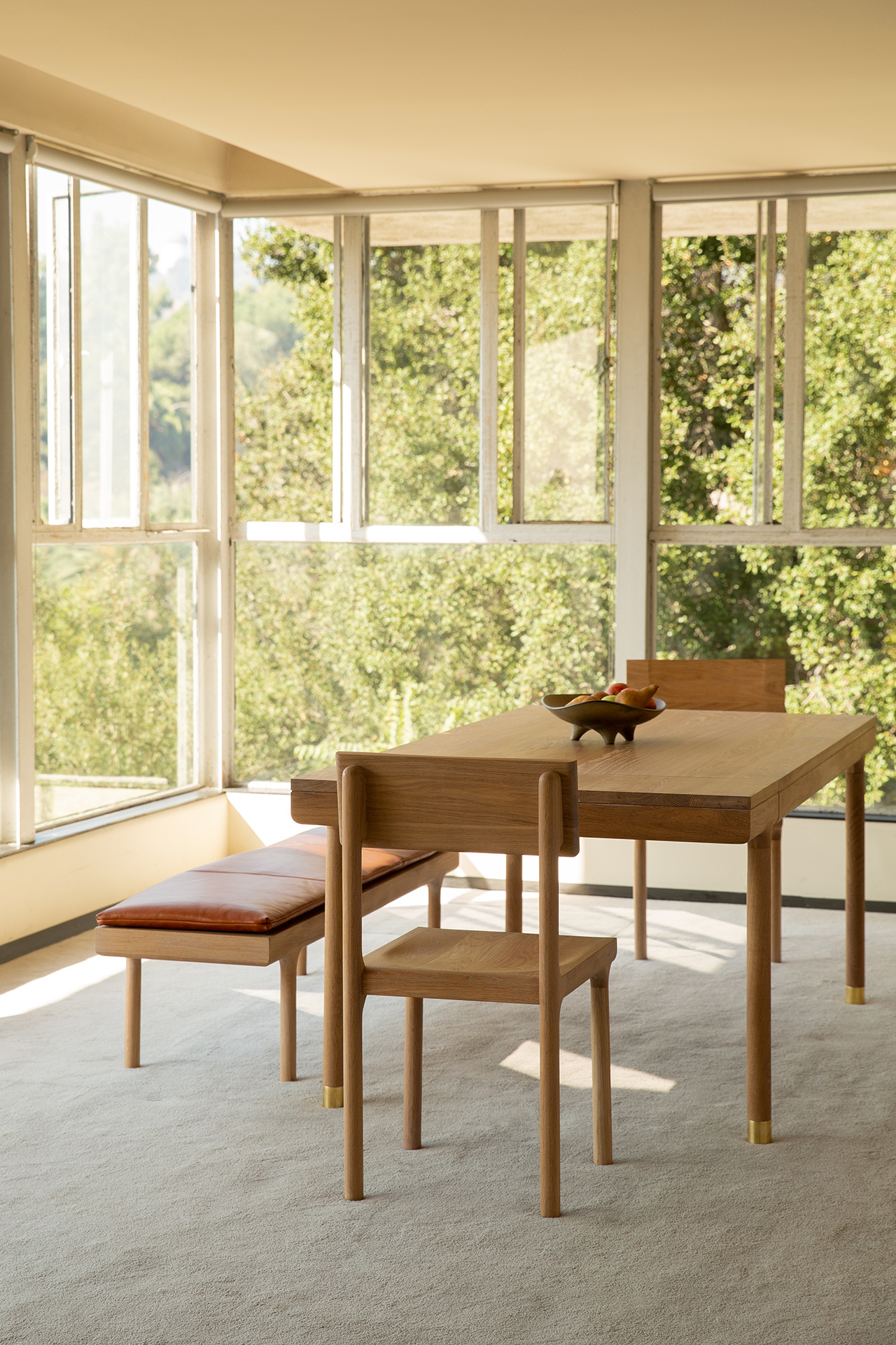 Oak dining table, dining chair, and leather topped bench in window-filled space