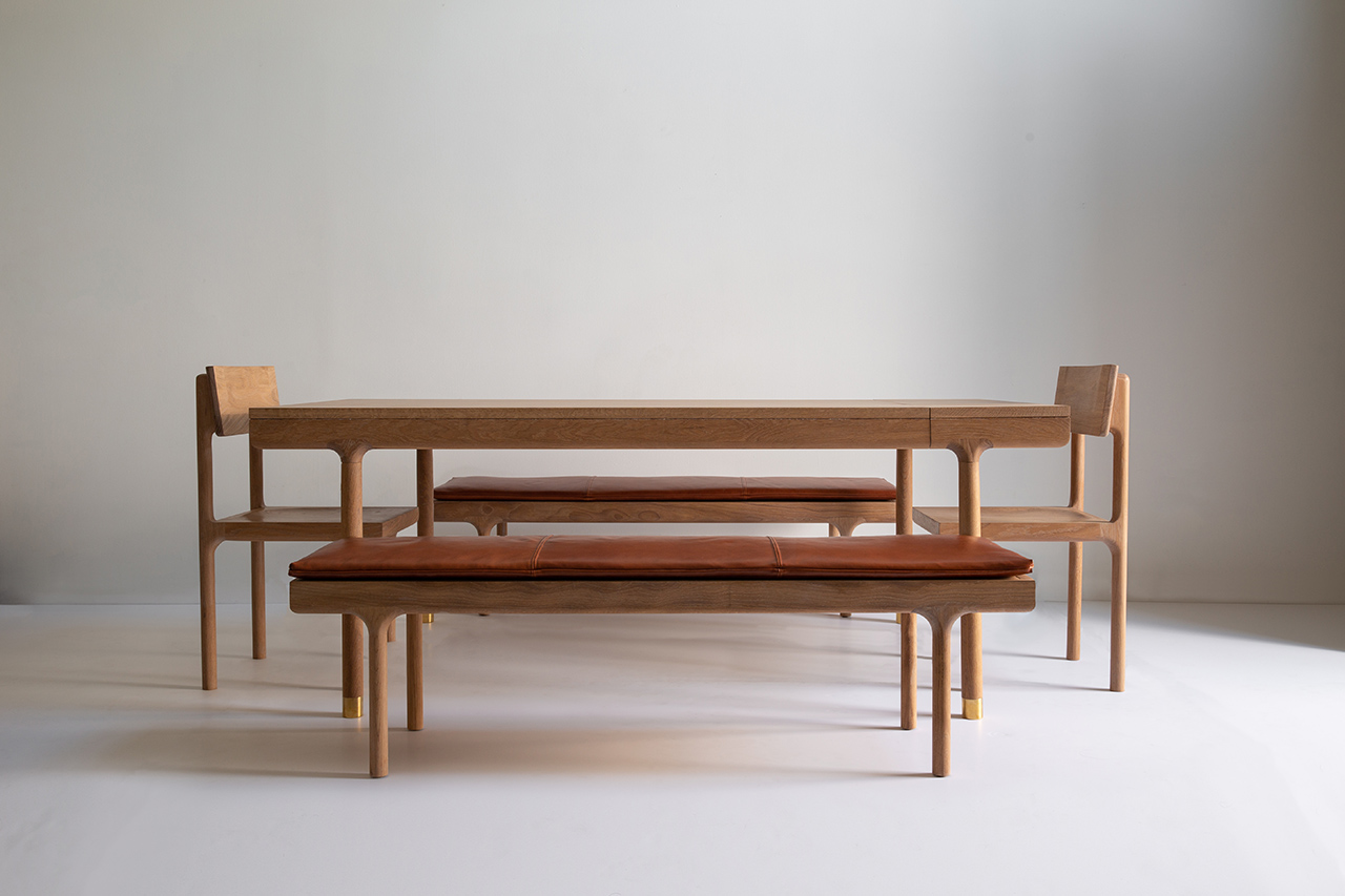 Oak dining table, dining chair, and leather topped bench in light space