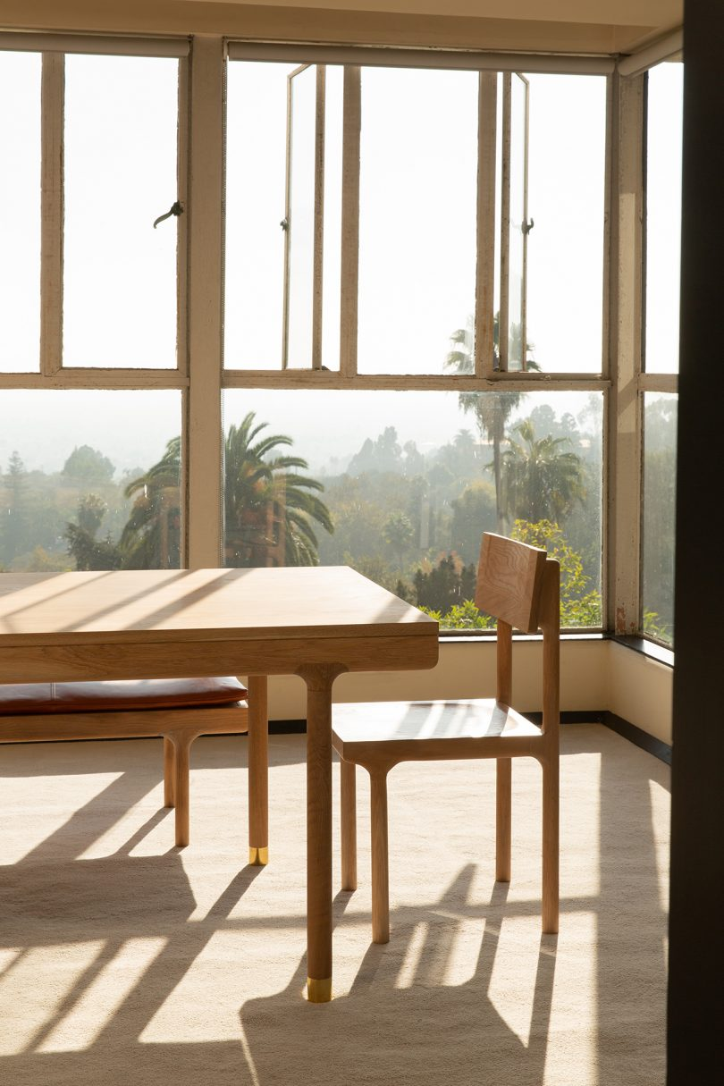Oak dining table and dining chair in window-filled space