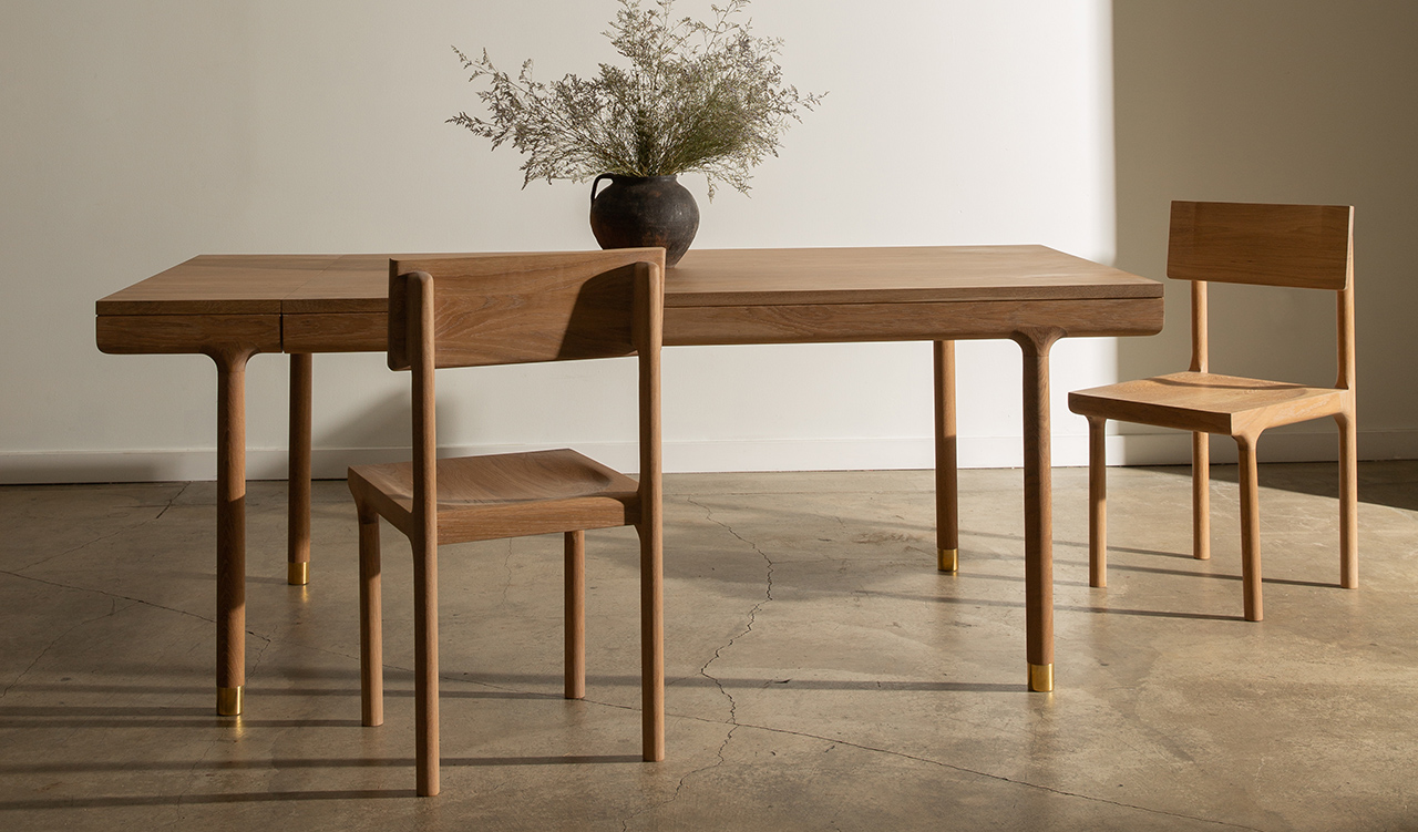Oak dining table with flower vase and two dining chairs in light space