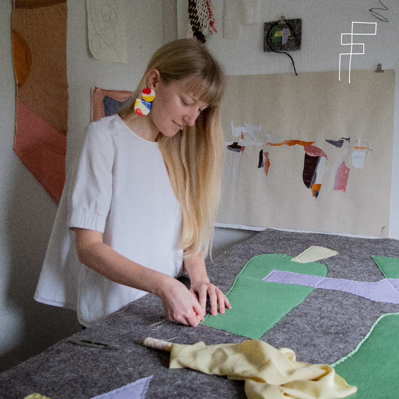 blonde woman in white shirt pinning a quilt on a table