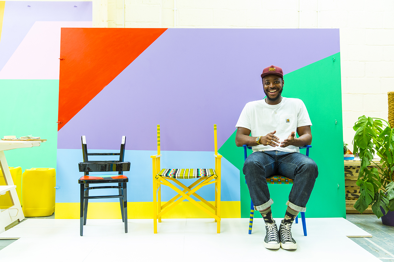 black man sitting in one of three chairs against a colorful geometric background