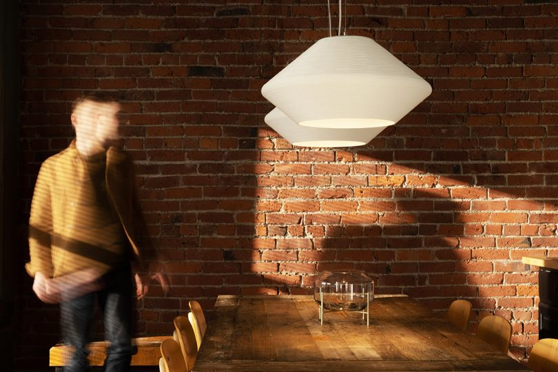 two white pendant lights hanging in dining space