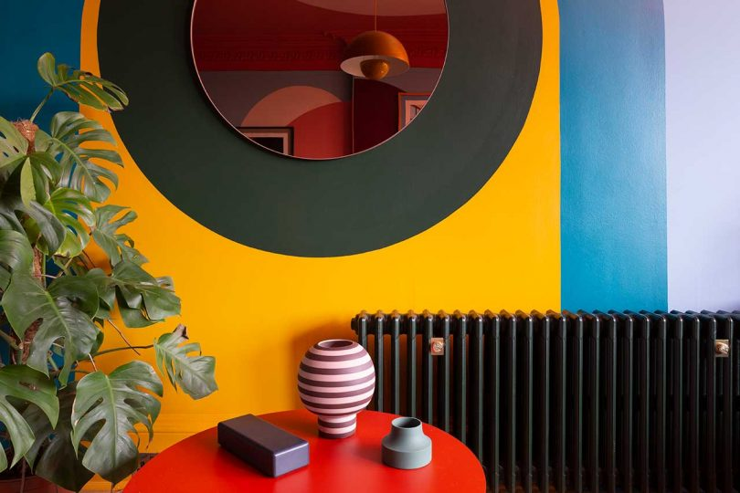 colorful wall with mirror and red table
